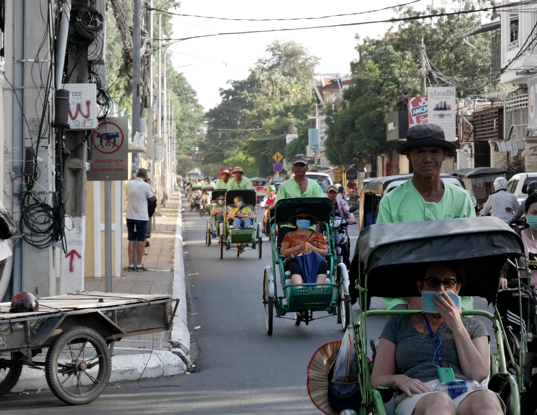 Un défilé de cyclo-pousse à Phnom Phen transportant des touristes.