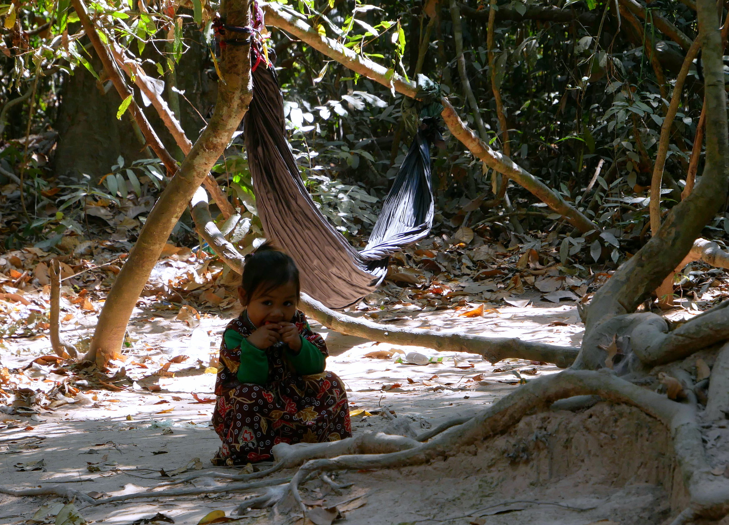 Enfant Khmer en tenue colorée qui mange un fruit.